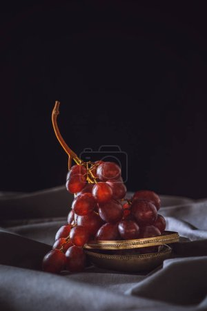 close-up shot of fresh red grapes on grey drapery on black