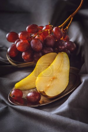 Photo for Close-up shot of sliced pear and red grapes on grey drapery - Royalty Free Image