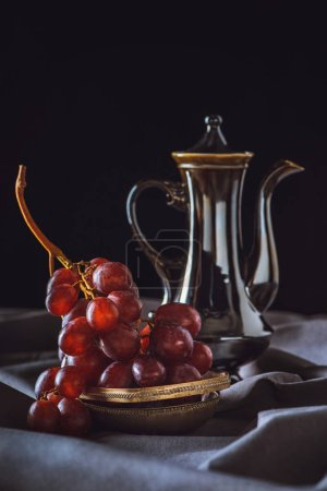 close-up shot of red grapes with vintage turkish teapot on black