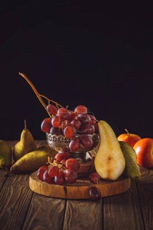 Nahaufnahme von reifen Trauben mit Birnen auf rustikalem Holztisch auf schwarz