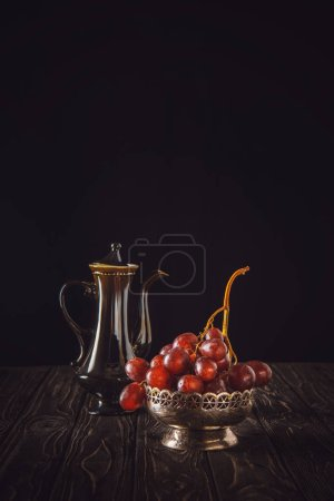 close-up shot of red grapes in vintage metal bowl and teapot on wooden table on black