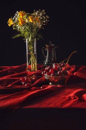Photo pour Nature morte de raisins dans un bol en métal avec des fleurs dans un vase et une théière turque sur draperie rouge - image libre de droit