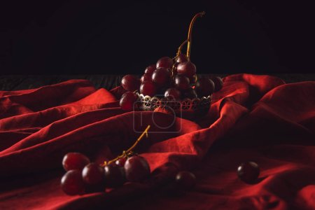 close-up shot of grapes in vintage metal bowl on red drapery on black