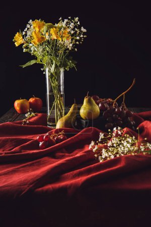 still life with fruits and flowers in vase on red drapery on black