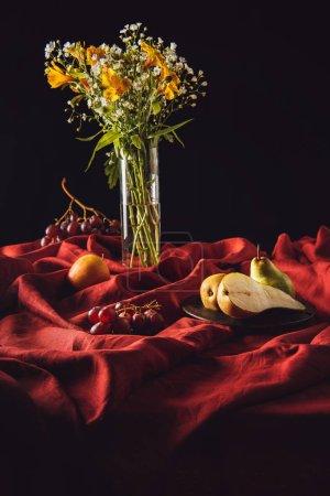 Stillleben mit verschiedenen Früchten und Blumen in der Vase auf rotem Tuch auf schwarzem Grund