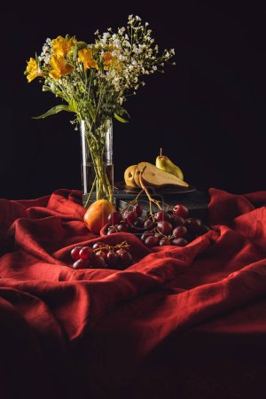 still life with various fruits and flowers in vase on red drapery on black
