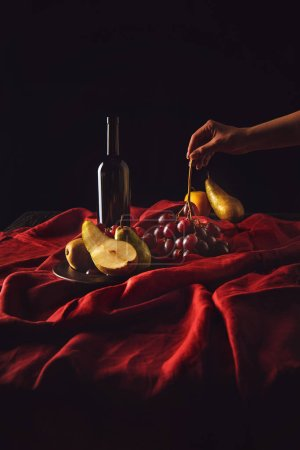 cropped shot of woman taking grapes from table with wine and pears on black