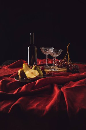 still life with pears, grapes and wine on red drapery on black