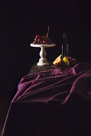still life with fruits and bottle of wine on burgundy drapery on black