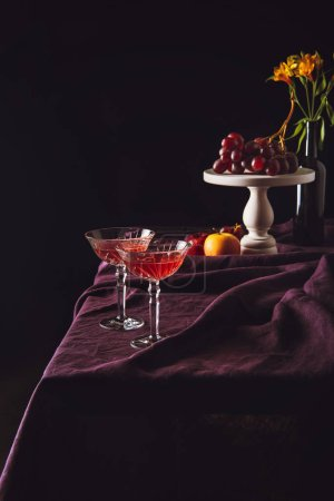 lead glasses of wine stand with grapes and apples on table with drapery on black