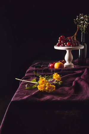 beautiful flowers lying on table with fruits on background