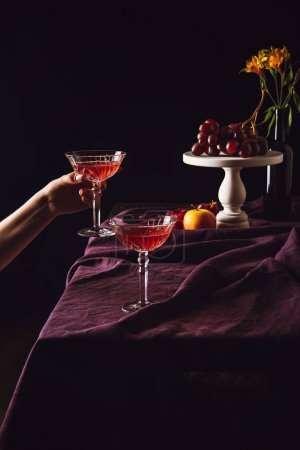 cropped shot of woman taking glass of wine from table with fruits on black