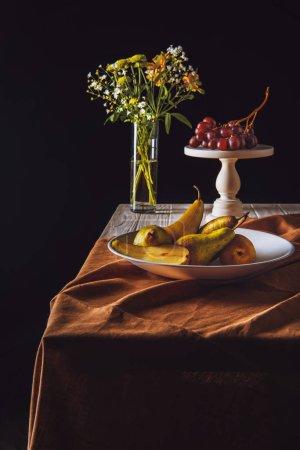 Teller mit Birnen und Ständer mit Trauben und Blumenvase auf Tisch auf schwarz