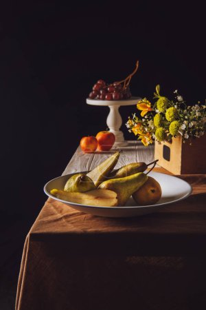 close-up shot of various fruits and field flowers on table on black