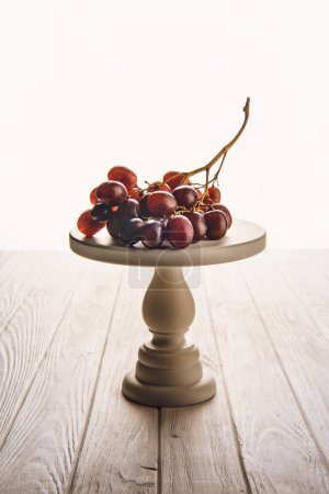 close-up shot of branch of grapes on stand on wooden table