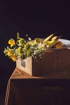 Nahaufnahme eines Straußes von Feldblumen mit Birnen in Schachtel auf schwarz