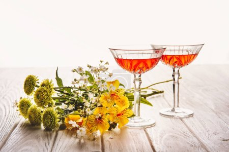 close-up shot of glasses of wine with field flowers bouquet on wooden table on white