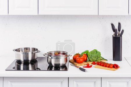 Photo for Ripe vegetables on kitchen counter, pans on electric stove in light kitchen - Royalty Free Image