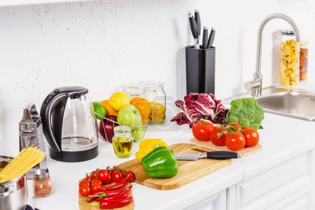 Photo for Ripe appetizing vegetables on kitchen counter in light kitchen - Royalty Free Image