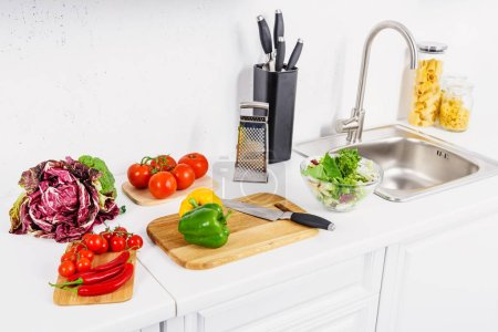 high angle view of bell peppers and knife on cutting board in light kitchen