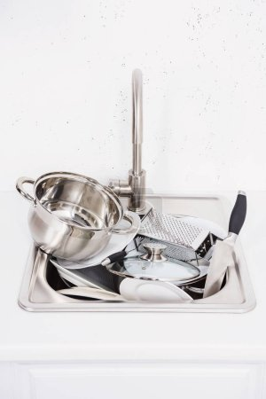 pile of dirty silver dishes in sink at kitchen
