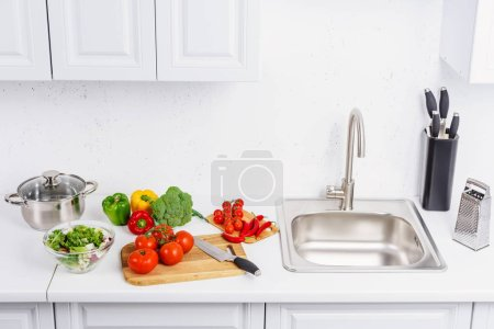 Photo for High angle view of tomatoes and chili peppers on cutting boards in light kitchen - Royalty Free Image