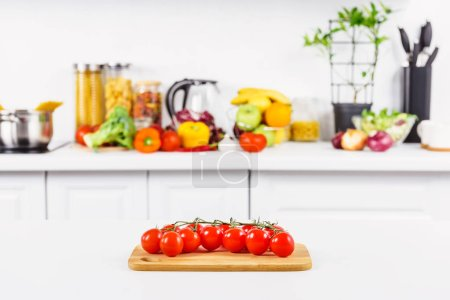 Photo for Ripe cherry tomatoes on cutting board in light kitchen - Royalty Free Image