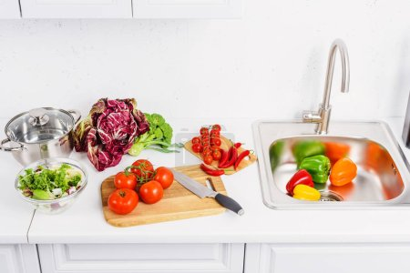 high angle view of ripe vegetables on cutting boards in light kitchen