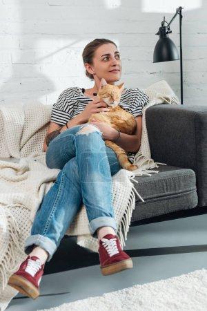 Photo pour Belle fille souriante caressant chat rouge et regardant loin à la maison - image libre de droit