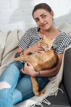 beautiful smiling young woman holding red cat and sitting on couch