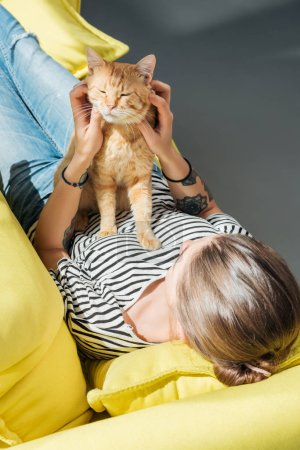 high angle view of girl playing with cute red cat while lying on yellow couch