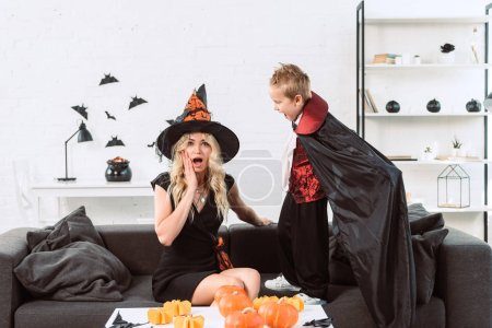 little boy in vampire costume screaming at mother in witch halloween costume at home