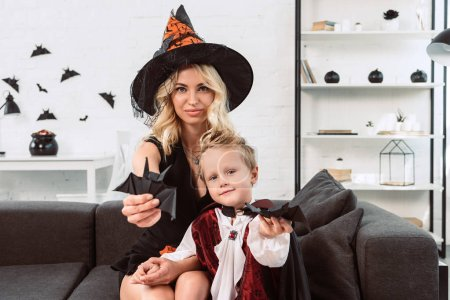 mother and little son in halloween costumes showing black paper bats on sofa at home
