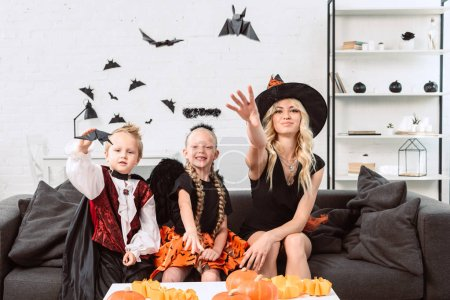 portrait of mother and kids in halloween costumes throwing black paper bats at home