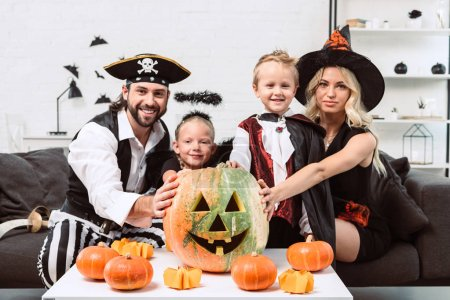 Foto de Retrato de la familia sonriente en varios trajes de Halloween en la mesa de café con calabazas en casa - Imagen libre de derechos
