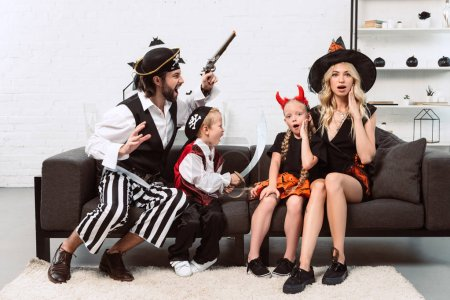 father and son in pirates costumes scaring mother and daughter on sofa at home