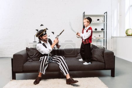 father and son in pirate costumes playing at home, halloween holiday concept