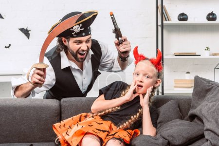portrait of daughter and father in halloween costumes playing at home