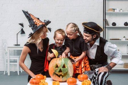 Foto de Familia en varios disfraces de Halloween en la mesa con calabazas en la cocina en casa - Imagen libre de derechos