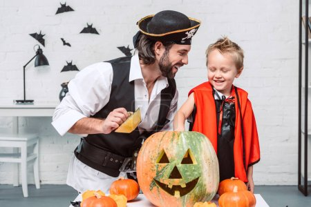 happy man in pirate costume and son in vampire halloween costume with pumpkin together at home