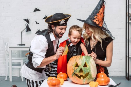 portrait of parents and son in halloween costumes looking into pumpkin at home
