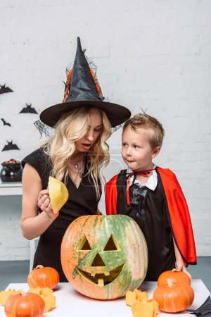 portrait of mother and son in halloween costumes at table with pumpkins at home