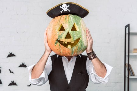 obscured view of man in pirate costume covering face with pumpkin, halloween holiday concept