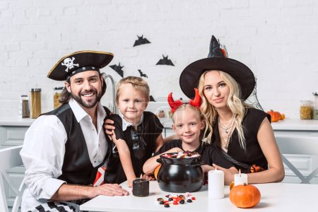Foto de Familia en varios trajes de halloween en la mesa con el pote negro con convites en cocina en casa - Imagen libre de derechos