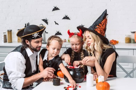 Foto de Familia en varios disfraces de Halloween en la mesa con olla negra con golosinas en la cocina en casa - Imagen libre de derechos