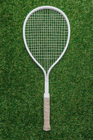 top view of white tennis racket lying on green grass