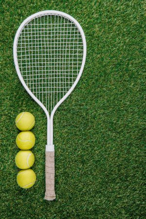 top view of tennis racket and balls of green grass