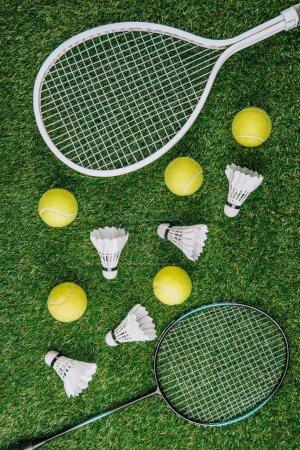 Photo pour Vue de dessus du matériel de badminton et de tennis disposé sur la pelouse - image libre de droit