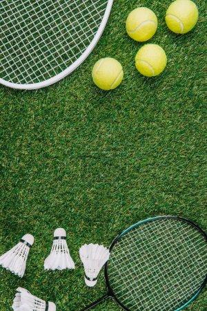 Photo pour Vue de dessus de l'équipement de badminton et de tennis disposé sur pelouse verte - image libre de droit