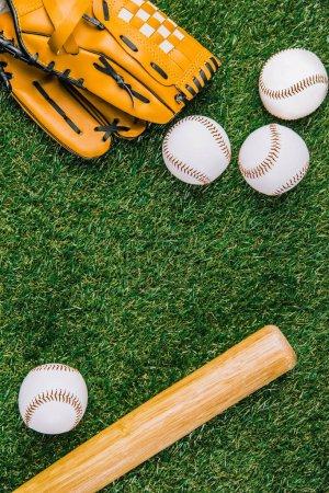 Photo pour Lay plat avec équipement de baseball disposé sur l'herbe verte - image libre de droit